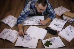 Uomo che lavora con il libro sul pavimento Fotografie Stock Libere da Diritti