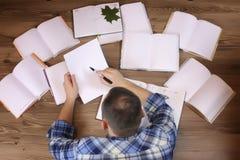Uomo che lavora con il libro sul pavimento Fotografie Stock