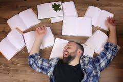 Uomo che lavora con il libro sul pavimento Immagine Stock Libera da Diritti