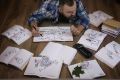 Uomo che lavora con il libro sul pavimento Immagini Stock