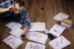 Uomo che lavora con il libro sul pavimento Fotografia Stock