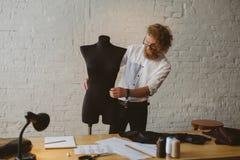 Uomo che lavora con il manichino in atelier fotografia stock libera da diritti