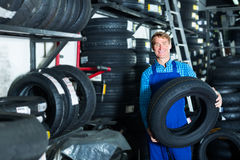 Uomo che lavora con il nuovo pneumatico per l'automobile immagini stock libere da diritti