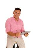 Uomo che lavora con il suo computer della compressa fotografia stock