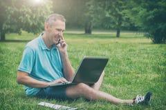 Uomo che lavora con il suo computer portatile nel parco fotografia stock