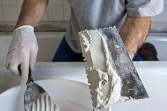 Uomo che lavora con il Trowel ed il mortaio che coprono di tegoli una parete fotografia stock libera da diritti