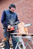 Uomo che lavora con la motosega sul tronco Immagini Stock