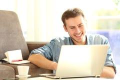 Uomo che lavora con un computer portatile a casa Fotografie Stock