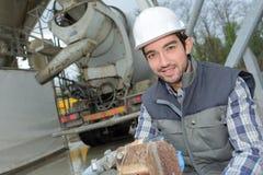 Uomo che lavora dietro il camion del cemento fotografie stock