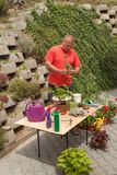 Uomo che lavora nel giardino Il giardiniere sfalsa i fiori Fotografie Stock