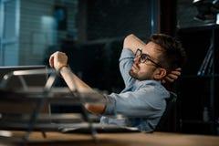 Uomo che lavora tardi nell'ufficio che controlla tempo fotografia stock