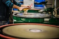 Uomo che lavora un vaso soffiato di vetro sul disco d'insabbiamento della silice Immagini Stock