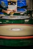 Uomo che lavora un vaso soffiato di vetro sul disco d'insabbiamento della silice Fotografie Stock