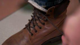 Uomo che lega i laccetti sulle scarpe marroni costose stock footage