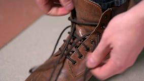 Uomo che lega i laccetti sulle scarpe marroni costose video d archivio