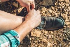 Uomo che lega i suoi stivali sulla montagna fotografia stock