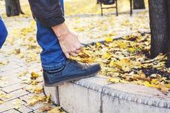 Uomo che lega laccetto nel parco di autunno Fotografia Stock Libera da Diritti