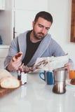 Uomo che legge il suo giornale durante la prima colazione di mattina Fotografia Stock Libera da Diritti