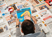 Uomo che legge la rivista di Charlie Hebdo Fotografia Stock
