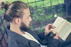 Uomo che legge un libro all'aperto fotografie stock