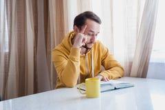 Uomo che legge un libro alla tavola Fotografia Stock Libera da Diritti