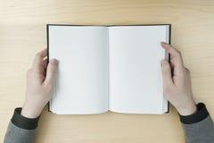 Uomo che legge un libro in bianco Fotografia Stock