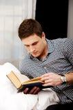Uomo che legge un libro nel suo letto Fotografia Stock