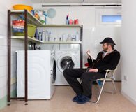 Uomo che legge un libro nella stanza di lavanderia Fotografia Stock Libera da Diritti