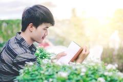 Uomo che legge un libro sul giardino Immagine Stock