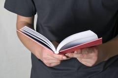 Uomo che legge un libro sulla priorità bassa bianca Immagini Stock