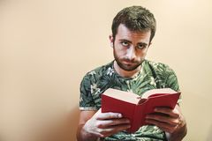 Uomo che legge un libro triste Fotografie Stock
