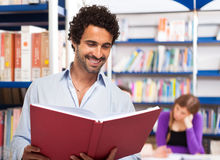 Uomo che legge un libro in una biblioteca Fotografia Stock