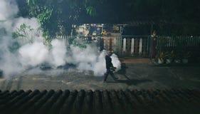 Uomo che libera fumo per riordinare le zanzare e per proteggere malaria in villaggio alla notte fotografia stock
