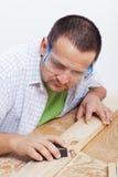 Uomo che lucida planck di legno Immagini Stock