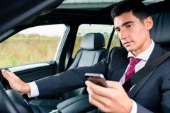 Uomo che manda un sms mentre guidando in macchina Fotografie Stock Libere da Diritti