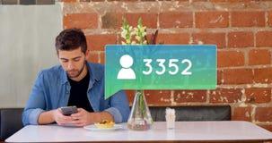 Uomo che manda un sms mentre mangiando pasticceria 4k video d archivio