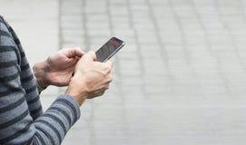 Uomo che manda un sms sulla pavimentazione del parco della città aperta fotografia stock libera da diritti
