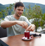 Uomo che mangia caffè all'aperto Fotografia Stock