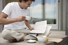 Uomo che mangia prima colazione e che legge giornale sul portico Fotografie Stock Libere da Diritti