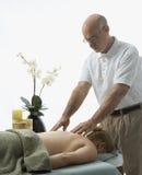 Uomo che massaggia donna. immagini stock