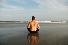 Uomo che meditating sulla spiaggia Fotografie Stock