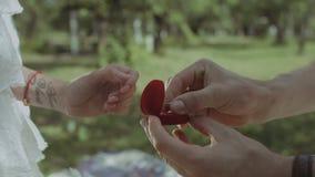 Uomo che mette anello di fidanzamento sulla mano della donna all'aperto stock footage