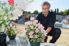 Uomo che mette i fiori freschi nel cimitero Fotografia Stock Libera da Diritti