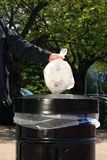 Uomo che mette immondizia in latta di A Fotografie Stock Libere da Diritti