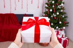 Uomo che mette la scatola del regalo di Natale sotto l'albero di Natale Fotografia Stock