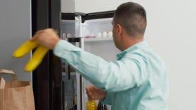 Uomo che mette nuovo alimento acquistato per dirigersi frigorifero video d archivio