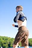 Uomo che mette sulla muta umida Fotografia Stock Libera da Diritti