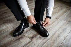 Uomo che mette sulle scarpe di cuoio nere eleganti Fotografie Stock Libere da Diritti