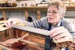 Uomo che misura i cerchi su una chitarra Fotografie Stock