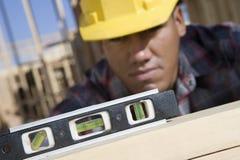 Uomo che misura a livello del legno Immagini Stock Libere da Diritti
